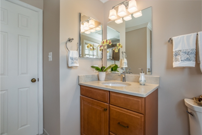 Woodbridge Hall Bathroom Remodel with Waypoint cabinets in Maple with spice finish and Park Harbor 3 light vanity fixture