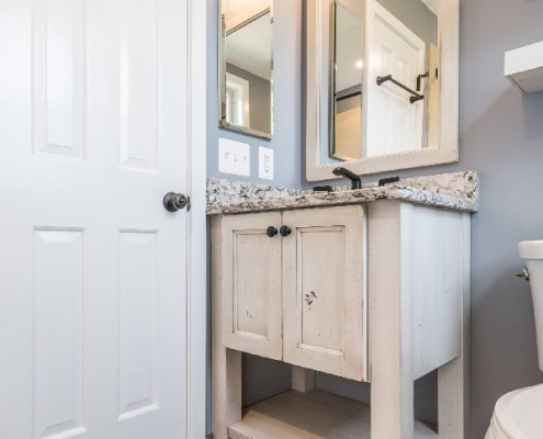 Farmhouse style bathroom remodel with wood look tile flooring and rustic vanity in Arlington, VA