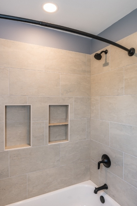 Bath remodel featuring tile shower surround and oil rubbed bronze fixtures