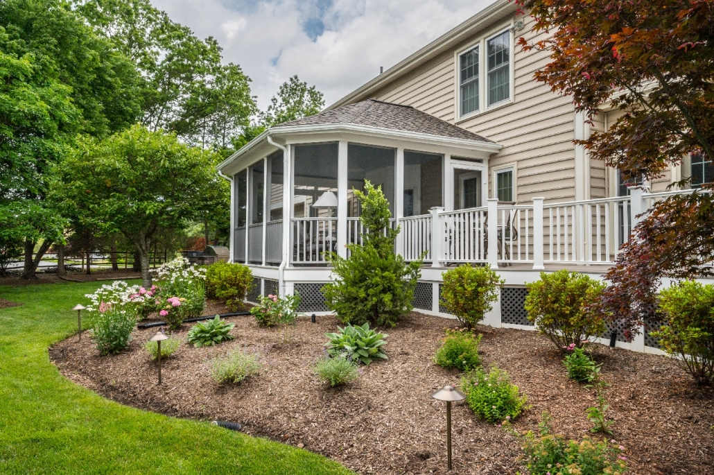 Custom screen porch with roofing, gutters, downspouts and outdoor lighting in Centreville