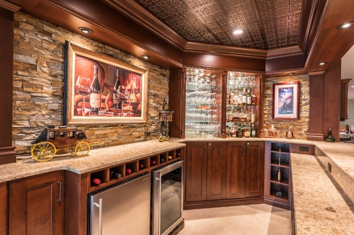 Deluxe custom bar with stone wall, showcase lighting, glass shelving and custom cabinets