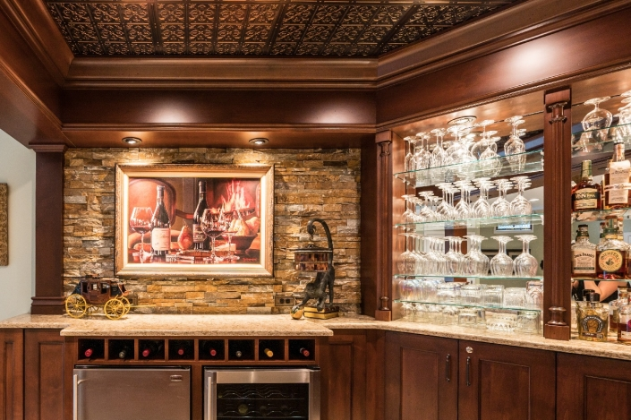 Haymarket ornate bar with stone accent wall and glass shelving with showcase lighting