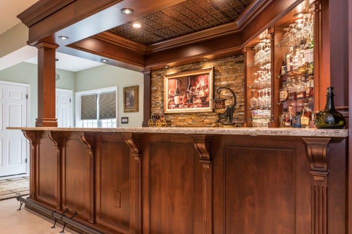 Traditional custom bar design-build basement remodel with copper stained alder wood cabinets and stone accent wall