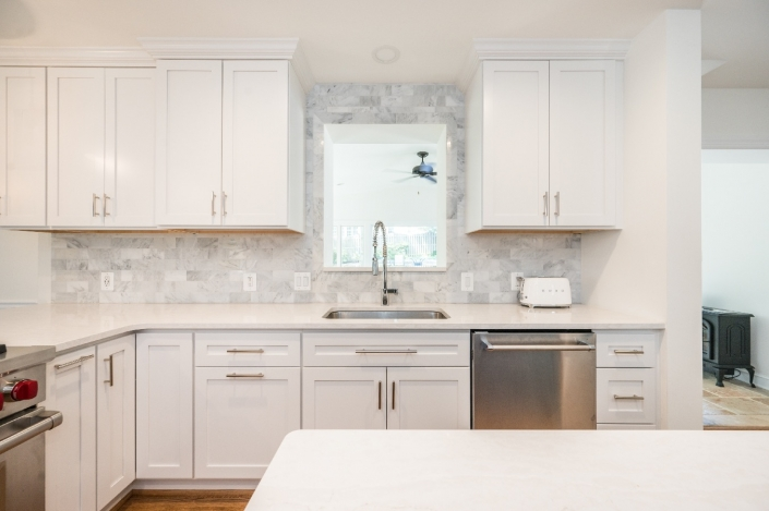 Alexandria, VA contemporary kitchen remodel with white cabinetry and natural stone backsplash and accent wall