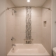 Vertical glass tile feature in shower stall with curved shower curtain bar in fairfax station bath remodel