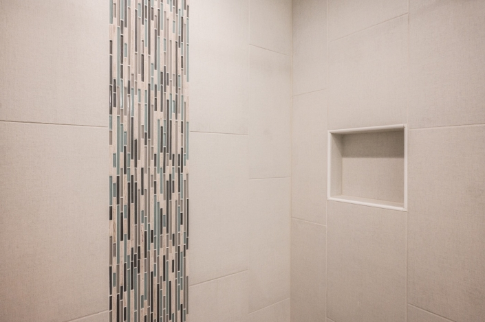 shower stall with vertical glass tile insert and recessed niche
