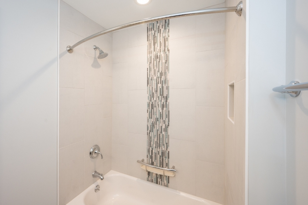 bathroom remodel in Fairfax Station with vertical glass tile feature and cream tiles