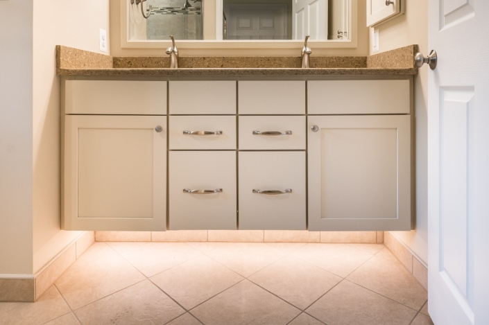 Koch vanity cabinets and Silestone countertop are paired with under cabinet lighting with floating feature