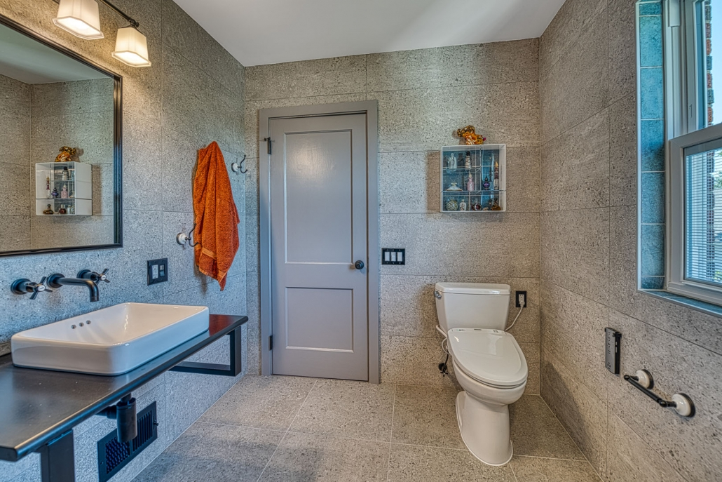 Custom Arlington bathroom remodel industrial chic with floating sink and stone tile walls