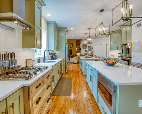 Custom kitchen remodel Gainesville va with sage green double islands and Viaterra Quartz countertops