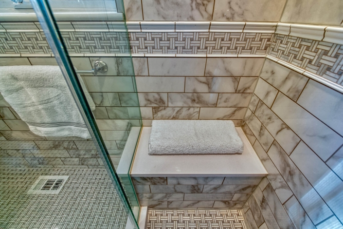 Bathroom remodel in Falls Church with Marble shower walls, flooring and bench seat