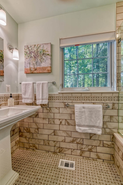 Bathroom remodel in Falls Church with Carrara Marble basketweave tile floor and Enchant tiles walls