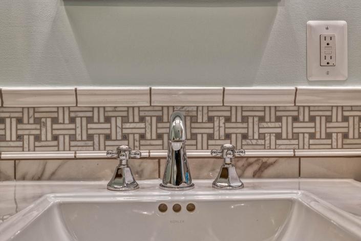Bathroom remodel in Falls Church featuring Carrara marble and Boca Raton widespread cross handle faucet